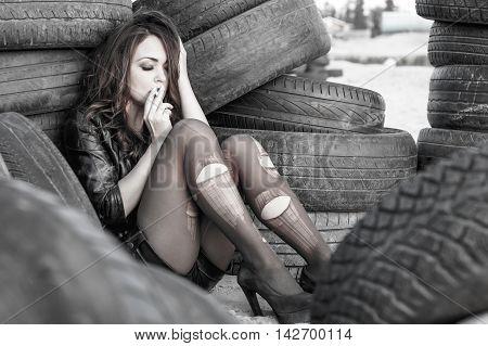 Woman Smoking Between An Old Tires