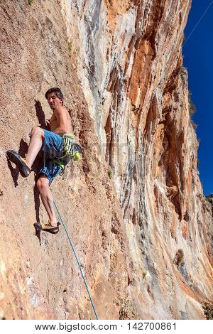 Mature Climber ascending high steep orange Rock with rope belay and many gear
