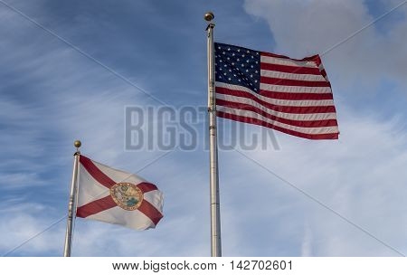 the American and Florida State flag, flying against a blue sky