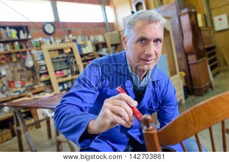 portrait of active senior carpenter sitting at his workshop