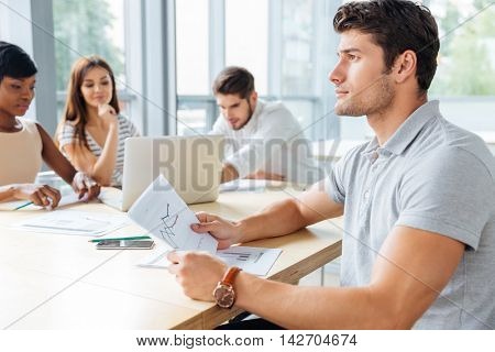 Thoughtful sucessful young businessman on business meeting in conference room