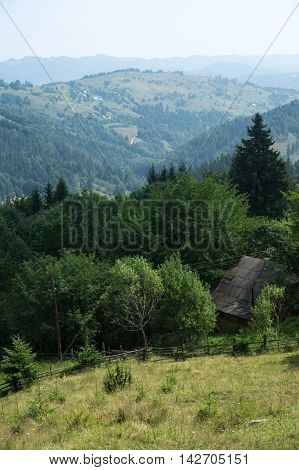 Village in the Carpathian Mountains. In the background the mountains in the haze. In the foreground is the old village hut
