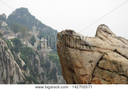A large rock with a blurred background of San Huang Zhai Monastery on top of Mount Song (songshan) near Dengfeng city in Henan Province China.