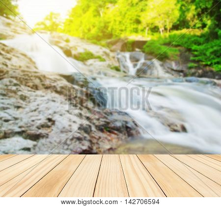 Wood table top on blurred water fall Can be used for display or montage you product
