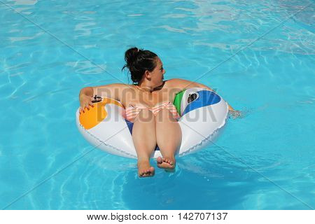 A young lady cooling off in a swimming pool while on vacation, 2016