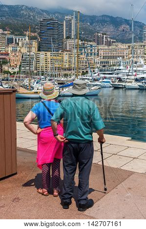 Monaco Monaco - July 30 2016: unidentified couple standing at the port of Monaco. Monaco is the 2nd smallest country in the world popular by the rich because of the tax policy