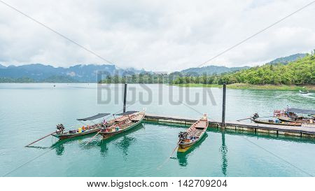 Boats are docked at the marina in Ratchaprapha dam Surat Thani Thailand.