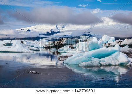 Ice lagoon in July. Summer vacation in Iceland. Icebergs and ice floes are reflected in the mirrored water of the ocean Bay
