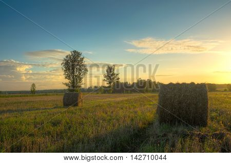 Sun just rises over a field of stubble with haystacks. August countryside landscape. HDR image.