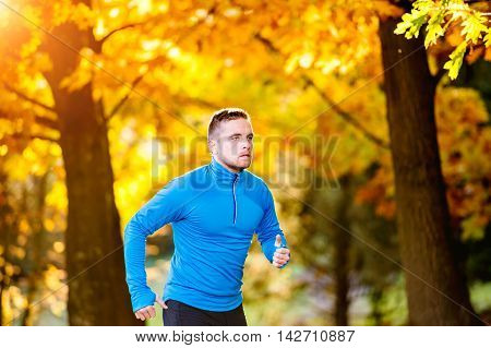Young Handsome Athlete Running Outside In Sunny Autumn Nature