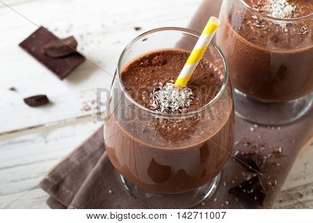 Chocolate banana smoothie or milkshake with coconut on white wooden table.