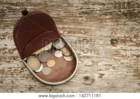 leather purse with Polish coins on wooden desk