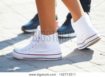 the feet of girl in white sneakers close-up