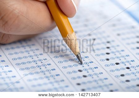 Student filling out answers to a test with pencil close up.