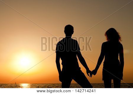 silhouette of a man and a woman watching the sunset in the sea