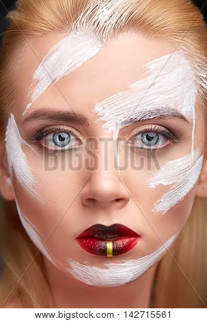 Portrait of young woman with creative makeup with dabs of white paint. Close up of a face of a girl with creative visage. Body art colorful.