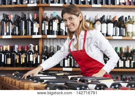 Portrait Of Saleswoman Arranging Wine Bottles In Rack