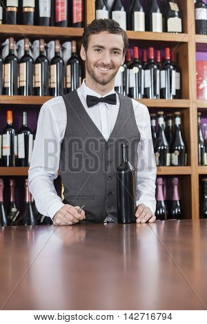 Confident Bartender With Wine Bottle Standing At Counter