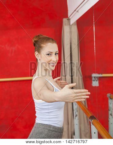 Portrait Of Smiling Ballet Dancer Performing In Studio