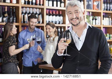 Happy Man Holding Wineglass With Friends In Background