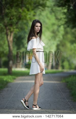 Full length portrait of a beautiful young caucasian woman in white dress with open shoulders clean skin long hair and casual makeup nature background