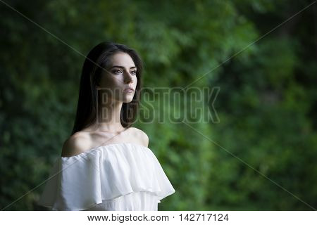 Portrait of a beautiful young caucasian woman in white dress with open shoulders clean skin long hair and casual makeup nature background