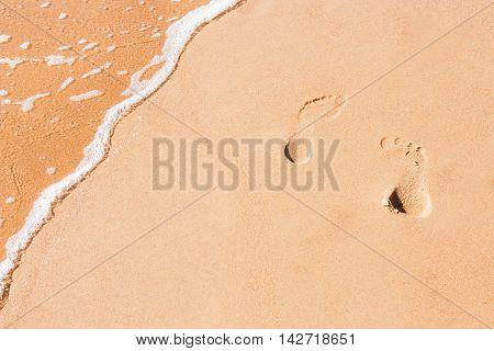 Abstract sand background with tracks of feet and sea water