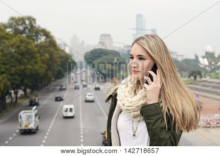 Portrait of a young beautiful woman talking on the phone. Outdoors. Urban scene.