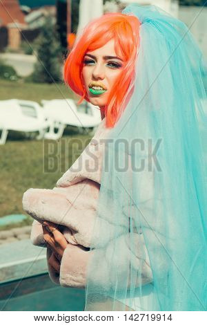 Young girl with pretty face bright professional makeup colorful eyeshadow yellow and green lips and orange hair wig wearing blue veil and fur coat