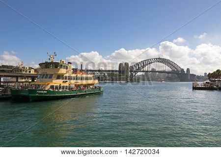 SYDNEY, AUSTRALIA - APRIL, 2016 : Tourists on Fishburn ferry docking at the pier near Sydney Harbour Bridge, steel arched bridge in Sydney, Australia on April 20, 2016.