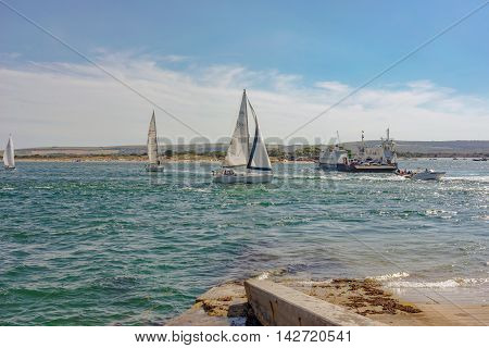 Sandbanks/UK. 14th August 2016. Leisure boats, windsurfers and speedsters enjoy the windy conditions of Poole harbour on a warm summer's day. The Sandbanks ferry, seen to the right provides a vehicular link between Studland and Sandbanks.
