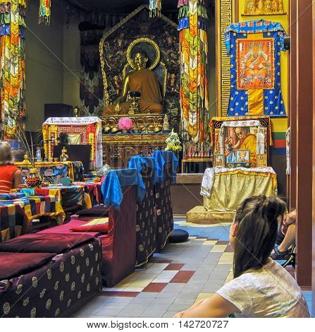 Saint - Petersburg, Russia - July 29, 2012: People in The Buddhistic Temple (Datsan Gunzechoinei). On the background is Shakyamuni Buddha Sculpture in altar
