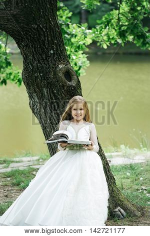 small girl kid with long blonde hair and pretty smiling happy face in prom princess white dress standing sunny day outdoor near water with book