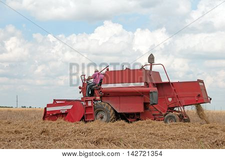 Amazing rural scene on autumn field with harvester