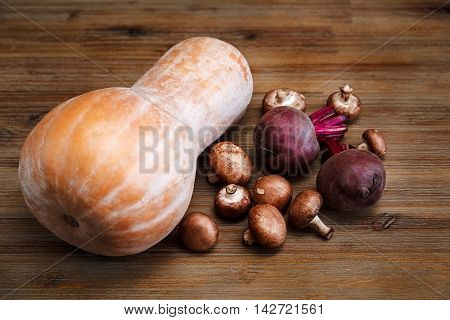 Purple Beets,Orange Pumkin,Fresh Mushrooms on the Wooden Table.Autumn Garden's Vegetable Background.Top View