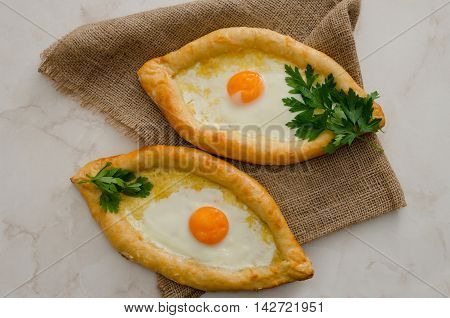 Two khachapuri with yolk on a light table and burlap