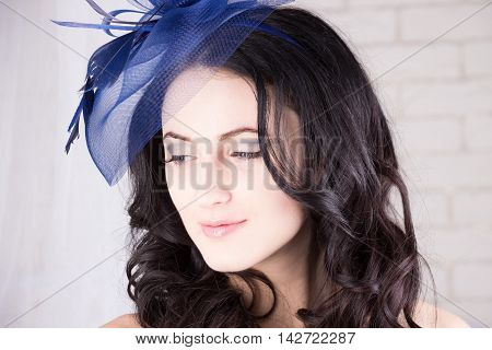 Dreamy girl with blue eyes looking down in blue hat