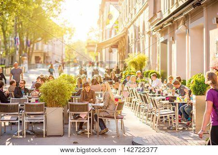 Ljubljana, Slovenia - May 6, 2016: People sit at the cafe in the old city centre in Ljubljana. Ljubljana is the capital of Slovenia and famous european tourist destination.