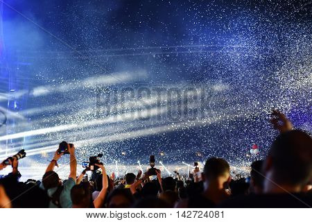 Throwing Confetti Over Crowd At Live Concert