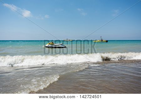 Sea waves with and motor boats in the background
