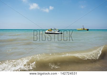 Sea waves with  motor boats in the background