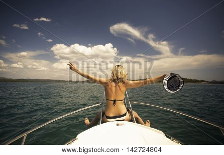 Young woman with hat sitting on the front of a sail boat admiring the view