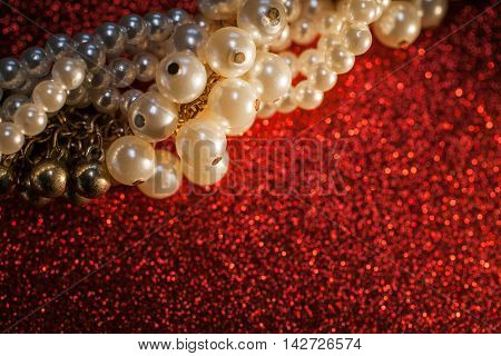 Close up of beautiful creamy pearls against a red glitter background