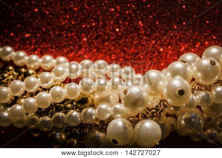 Beautiful creamy and golden pearls on a red sparkling background. Luxury jewelry background