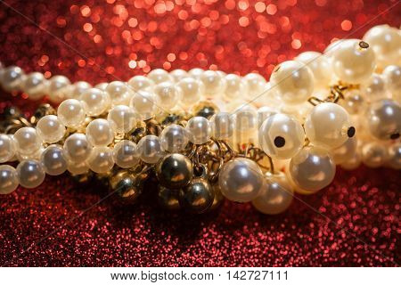 Beautiful creamy and golden pearls against a red glitter. Luxury jewelry background