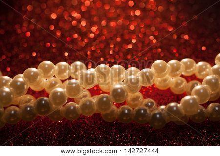 Beautiful creamy pearls on a red glitter. Luxury jewelry background