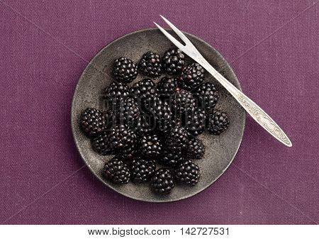 Blackberries plate on magenta tablecloth. Top view