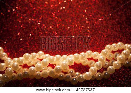 Beautiful creamy pearls on a red glitter. Luxury jewelry shiny background