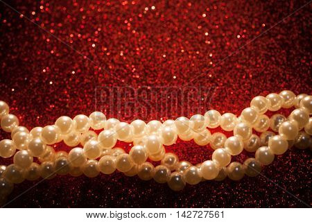 Beautiful creamy pearls on a red glitter shiny background