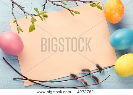Blank paper sheet with easter eggs and pussy willow branches on blue painted wooden background